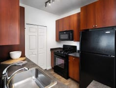 Kitchen with Black Appliances, Maple Cabinetry, and Hard Surface Vinyl Plank Flooring