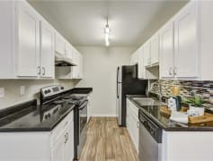 Newly renovated kitchens feature a tile back-splash, granite inspired counters, and silver appliances
