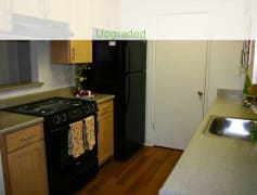 Upgraded Apartment Kitchen with Hard Surface Plank Flooring and Black Appliances