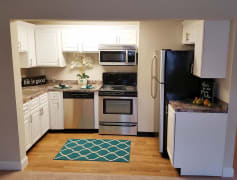 Newly renovated kitchens featuring wood-style flooring, granite-style counters and stainless steel appliances.