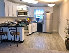 Updated kitchens with black fusion counter tops, wood-style flooring, and stainless steel appliances.