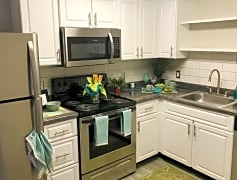 Newly remodeled kitchens featuring black fusion counter tops, wood-style flooring, and stainless steel appliances.
