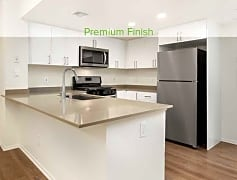 Premium finish kitchen with quartz countertops, stainless appliances, new cabinetry, and hard surface vinyl plank flooring in select homes (representative photo)