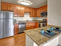 A kitchen with stainless steel appliances and granite conutertops