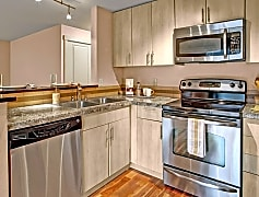 A kitchen with stainless steel appliances, stone countertaps, a small breakfast bar, and lots of cabinet space