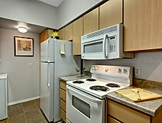 A kitchen with light cabinetry and white appliances