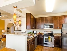 A kitchen with granite counters, dark cabinetry, and stainless steel appliances