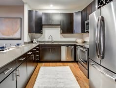 spacious kitchen with dark brown cabinetry granite counters and stainless steel appliances
