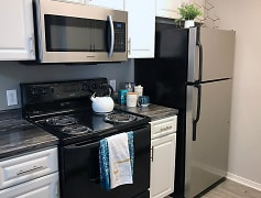 Newly renovated kitchens featuring stainless steel and black appliances and modern white cabinetry.