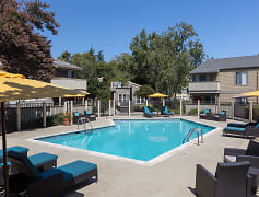 Outdoor swimming pool with sundeck, lounge chairs, and umbrellas.