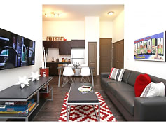 Fully furnished living in every floor plan. Living room furniture included: couch, side chair, coffee table, side table, entertainment center with smart TV mounted on the wall.