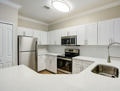 Image of a kitchen with wrap around quartz counters and a ceramic backsplash.