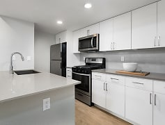 Newly renovated kitchen with quartz countertops, stainless steel appliances, tile backsplash, new cabinetry, and hard surface plank flooring (in select homes)