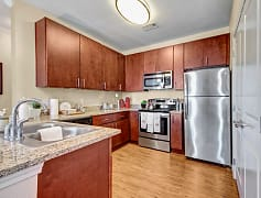 A large kitchen with granite countertops and stainless steel appliances