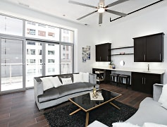 Villa 303 living room featuring 14 Ft ceilings, floor-ceiling windows with access to private balcony, built in wet-bar with custom cabinetry and quartz counter-top, upper/lower accent lighting, and custom tile flooring.