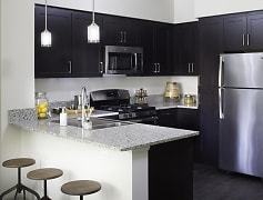 Warm chestnut kitchen provides all new black and silver appliances including a gas range stove