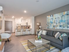 Staged living room with hardwood style flooring, and AC unit. Kitchen with breakfast bar and stainless steel appliances.