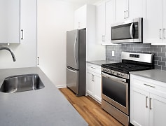 Newly renovated kitchen with quartz countertops, tile backsplash, stainless steel appliances, and hard surface plank flooring
