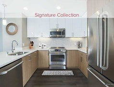 Signature Collection Kitchen with Quartz Stone Countertops, GE Cafe Series Stainless Steel Appliances, Two-Tone Cabinetry, Marble Tile Backsplash, and Hard Surface Vinyl Plank Flooring