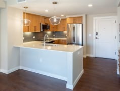 Modern finishes include white quartz countertops and glass tile backsplash