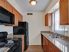 A kitchen with granite countertops, lots of cabinets, and sleek black appliances