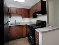 Kitchen with cherry cabinetry, black appliances, and hard surface plank flooring