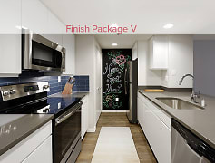 Kitchen with quartz countertops, new cabinetry, accent chalkboard wall, and stainless steel appliances (in select homes)