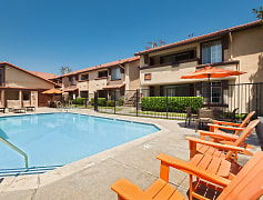 Swimming pool with lounge chairs surrounded by apartment building.