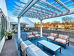 Our outdoor lounge features both table and lounge seating under a pergola with string lights and speakers