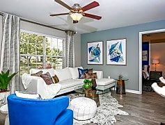 Spacious, open living room featuring wood-style flooring, a ceiling fan, and large window.