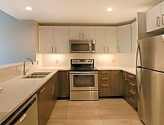 Modern kitchen with stainless steel appliances and quartz countertops