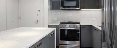 22 East First Street newly renovated apartment kitchen featuring quartz countertops, stainless steel Whirlpool appliances, hard surface flooring, and new cabinetry (in select homes)