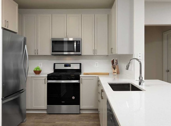 Finish Package IV Kitchen with new grey cabinetry, white quartz countertops, stainless steel appliances, tile backsplash, and hard surface flooring