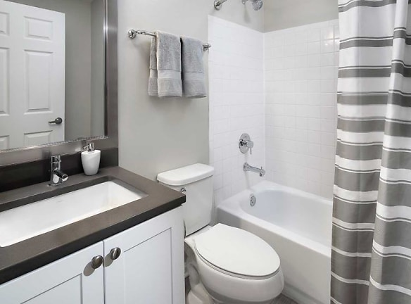 Newly renovated Finish Package II bath with white cabinetry, grey quartz countertops, and hard surface flooring
