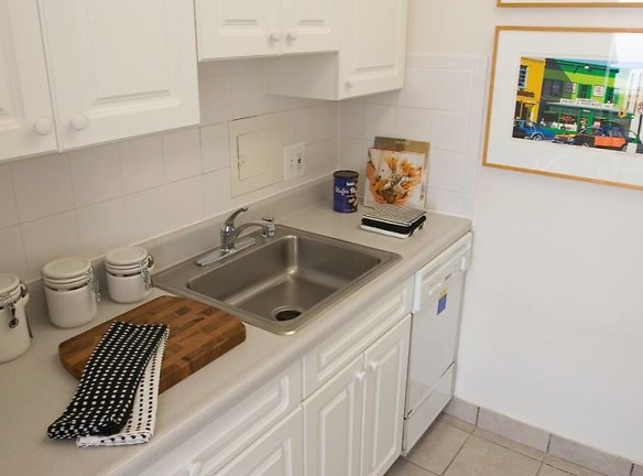 Studio apartment kitchen with large stainless steel sink, dishwasher and white cabinets