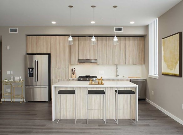 Signature Collection penthouse kitchen with oak cabinetry and undercabinet lighting, white quartz countertops and backsplash, upgraded stainless steel appliances, and hard surface flooring