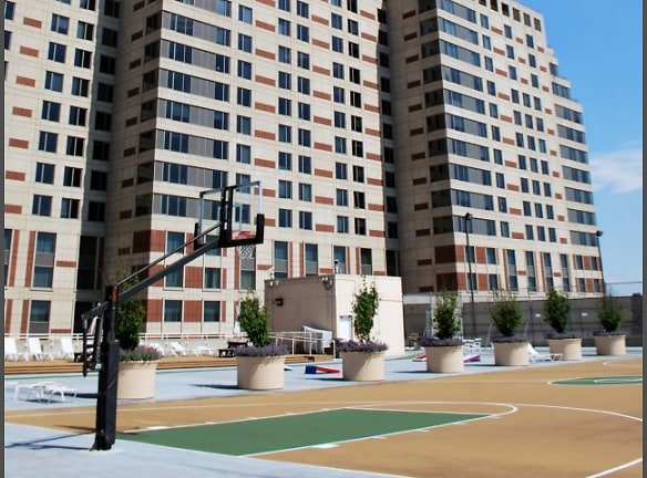 Rooftop sports deck with full basketball and tennis courts, grills and a lounging area