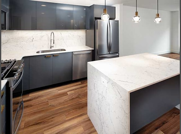 22 East First Street newly renovated apartment kitchen featuring new pendant lighting, under cabinet lighting, hard surface plank flooring, and new cabinetry (in select homes)