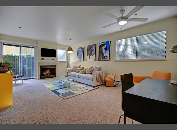Living room with couch, desk, armchair, large windows, ceiling fan, fireplace, and sliding glass door out to a patio