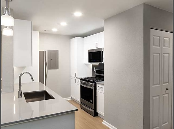 Kitchen with stainless steel appliances, quartz stone countertops, and hard surface flooring