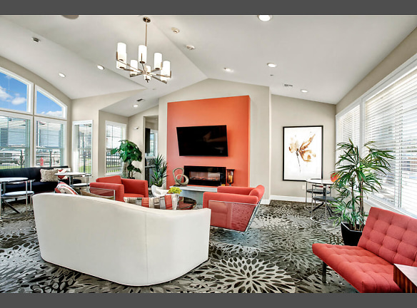 A large, shared space with couches, chairs, a flat screen TV and fireplace for resident use