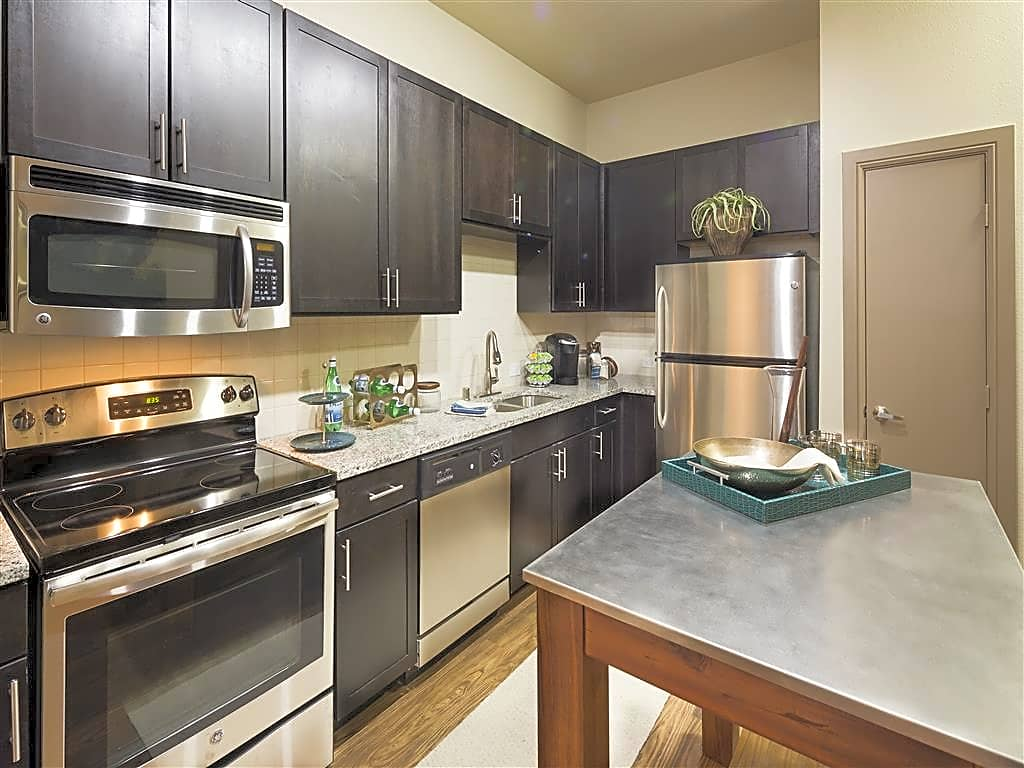 Kitchen with granite counter-tops, sleek espresso-colored cabinetry, and stainless steel appliances