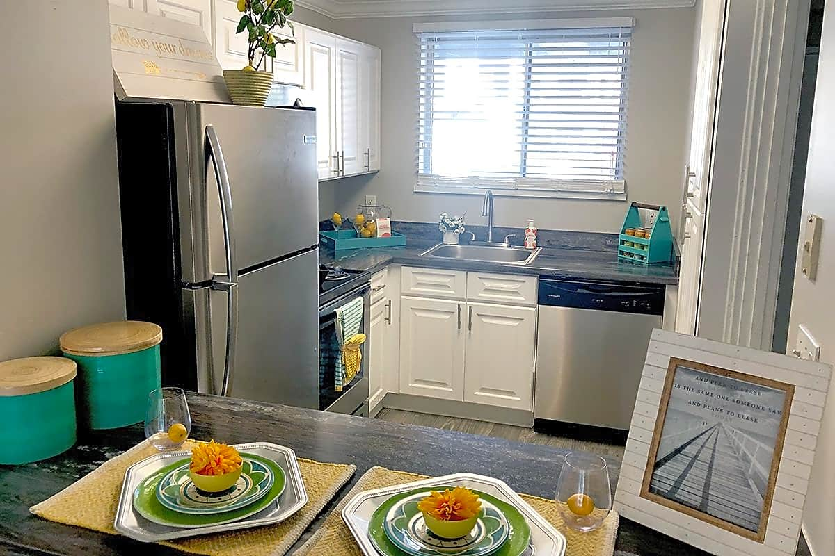 """Updated kitchens featuring """"classy grey"""" finish countertops, wood-style flooring, and a breakfast bar."""
