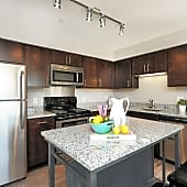 Full kitchen with large center island, overhead lighting, and stainless steel appliances
