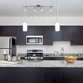Pulse offers modern kitchens in two color schemes. Above is Espresso. All kitchens include Energy Star appliances, granite countertops, and spacious pantries with adjustable shelving.