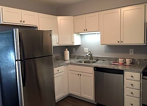 Renovated kitchen offering modern white cabinetry, granite counter tops and stainless steel appliances.