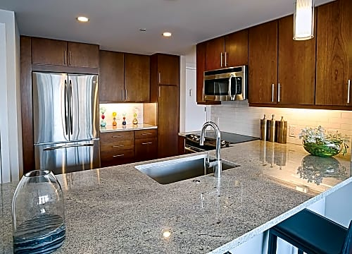Spacious Kitchens With Breakfast Bar, Pendant Lighting, Stainless Steel  Appliances, And Cherry Wood