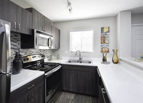 Newly updated kitchens include stainless steel appliances and a glass tile backsplash