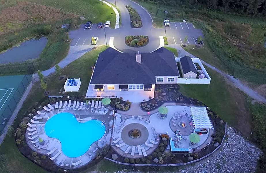 Aerial view at dusk of Shelter Cove clubhouse, pool, and patio with fireplace and fountain