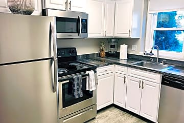 Newly renovated kitchens featuring black fusion counter tops, wood-style flooring, and stainless steel appliances.